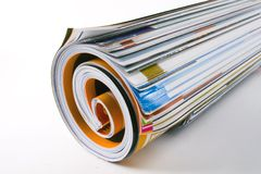 Weekly read. A close-up of a rolled magazine on a white background Stock Image