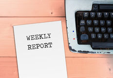 Weekly report on paper. With typewriter on wood table Stock Photography