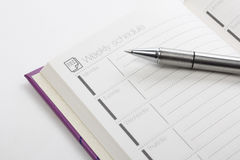 Weekly schedule. With pen on white royalty free stock photography