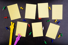 Weekly schedule with pins and two pens. On black table Stock Image