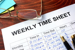 Weekly time sheet. Paper with weekly time sheet on a table Stock Image