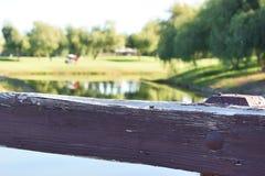 Weelderige groene golfcursus viewd van een houten brug bij een exclusief park als het plaatsen stock foto