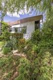 Weelderige tuin en een losgemaakt huis stock foto's