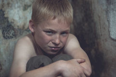 Weeping boy curled up in corner Stock Photography