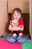 Weeping Boy with Teddy Bear. Small boy crying in a cardboard box with teddy bear Stock Images