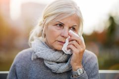 Weeping old woman wipes her eyes with tissue. Unhappy senior woman wipes her eyes with a tissue stock image