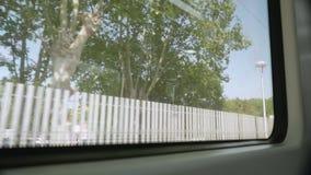 Weergave van de treinstand vanaf het raam van het treinvervoer dat op het station aankomt stock videobeelden
