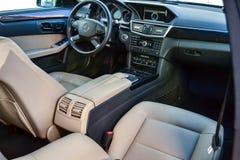 Weergeven aan het witte binnenland van Mercedes-e-Klasse W212 met dashboard, klok, media systeem, voorzetels en shiftgear daarna stock afbeeldingen