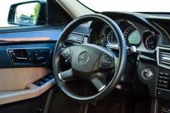 Weergeven aan het witte binnenland van Mercedes-e-Klasse W212 met dashboard, klok, media systeem, voorzetels en shiftgear daarna stock foto
