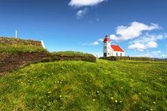 Weergeven bij de kerk van Modrudalur-regeling in Oostelijk Eiland, groene weide en de muur van traditioneel islandic gras stock fotografie