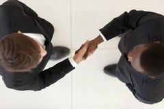 Weergeven direct van boven diverse zakenlieden die in kostuums handen schudden royalty-vrije stock afbeelding