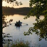 Weergeven door bomen op het meer met een boot en een zonsonderganghemel royalty-vrije stock foto's