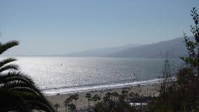 Weergeven door de bomen aan de oceaankust Santa Monica Beach De mensen baden Zeilboot die op de golven varen De warme Zomer stock videobeelden