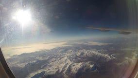 Weergeven door een vliegtuigvenster de vliegtuigvleugel boven sneeuwbergen stock video