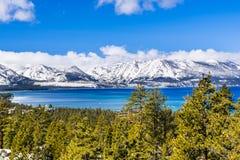 Weergeven naar Meer Tahoe op een zonnige duidelijke dag; de sneeuw behandelde Siërra bergen op de achtergrond; altijdgroene bosse stock fotografie