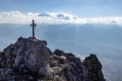 Weergeven over een bergpiek met een topkruis neer aan Innvalley en Innsbruck in Oostenrijk in de herfst zoals die van a via Ferra royalty-vrije stock afbeelding