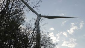 Weergeven van achter de bomen op elektrische windmolen Mening van neer aan omhoog stock videobeelden