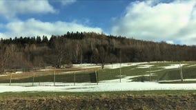 Weergeven van berg van het autoraam Berg in de vroege lente, sneeuw en groen gras tegen blauwe hemel stock footage