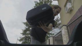 Weergeven van binnenuit auto van de vermoeide jonge bedrijfsmens die van werk aankomen die thuis zijn zak van autoboomstam het ne stock video