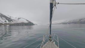 Weergeven van boogschip die op sneeuwbergen en klippenlandschap varen in overzees stock video
