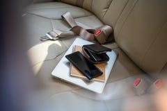 Weergeven van buiten de auto bij kostbaarhedenportefeuille, beurslaptop of computernotitieboekje, creditcard en mobiele telefoon, stock foto