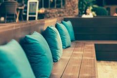 Weergeven van comfortabele hoeklaag met vele hoofdkussens buiten op zolderbalkon met heldere zonstralen royalty-vrije stock fotografie