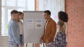 Weergeven van commercieel team die op in zolderkantoor werken De jonge gemengde rasgroep mensen brengt palm op centrum samen lang stock video