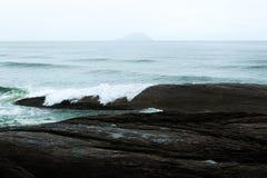Weergeven van de Atlantische Oceaan met golven die rotsen in bewolkte dag verpletteren royalty-vrije stock foto's