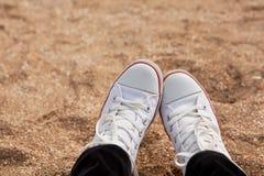Weergeven van de benen in witte tennisschoenen op achtergrond van shell strand Atmosferische, melancholische stemming, vage achte royalty-vrije stock fotografie