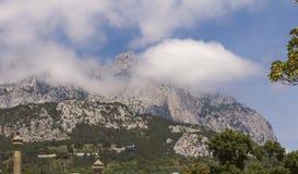 Weergeven van de bergpieken van AI-Petri tegen de blauwe hemel en de witte wolken crimea stock afbeelding