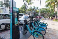 Weergeven van de blauwe die Biki-fietsen van het huuraandeel op de straat in Waikiki, Oahu, Hawaï worden opgesteld royalty-vrije stock afbeelding