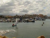Weergeven van de dijk van Chania door de baai met een klein varend jacht onder een wit zeil en een sombere hemel stock afbeelding
