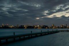 Weergeven van de horizon van Rotterdam in Nederland met een meer en pijler in de voorgrond stock foto's