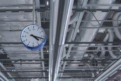 Weergeven van de klok die van het plafond tegen de achtergrond van ventilatiepijpen hangt stock afbeelding