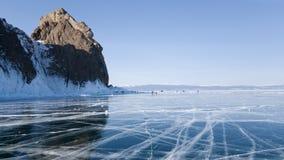 Weergeven van de kust van Olkhon-eiland van het bevroren meer Baikal Barsten in het ijs van het meer Panorama van meer Baikal stock afbeeldingen