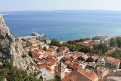 Weergeven van de rode daken van het historische centrum van Omis Kroatië tegen het overzees royalty-vrije stock foto's