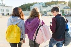Weergeven van de rug op drie middelbare schoolstudenten met rugzakken stock afbeelding