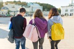 Weergeven van de rug op drie middelbare schoolstudenten met rugzakken stock fotografie