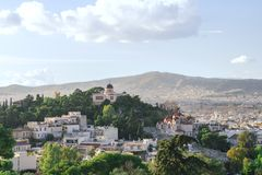 Weergeven van de stad van Athene, de kerk en de bergen van de Akropolis Groene bomen en blauwe hemel royalty-vrije stock fotografie