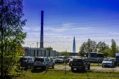 Weergeven van de stad, de grote pijpen en een grote wolkenkrabber op de achtergrond van het Parkeerterrein erachter royalty-vrije stock afbeeldingen