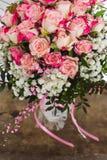Weergeven van een boeket van verse pastelkleur roze rozen met een roze boog op rustieke houten achtergrond stock foto