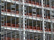Weergeven van een grote de bouwontwikkeling in aanbouw met staalkader en balken ondersteunend de de metaalvloeren en hijstoestell royalty-vrije stock afbeelding