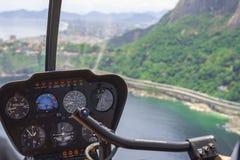 Weergeven van een helikoptercockpit die over Rio de Janeiro vliegen Cockpit met instrumentenpaneel Kapitein in de vliegtuigencock royalty-vrije stock foto
