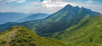 Weergeven van een hoge bergketen met een rotsachtige piek en een weg langs zijn helling Groene die bergvallei, met bossen wordt o stock foto