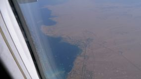 Weergeven van een hoogte op een toevluchtstad op de kust van het overzees van een vliegtuigvenster stock videobeelden