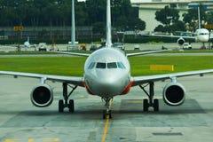 Weergeven van een Jetstar-Luchtbusa320 vliegtuig die aan parkerenpoort belasten in Changi Luchthaven, Singapore stock fotografie