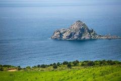 Weergeven van een klein rotsachtig eiland in het Japanse Overzees royalty-vrije stock fotografie