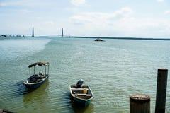 Weergeven van een mens door de pier die kabel van zijn boot beveiligen aan een houten pier Mening van een houten pier royalty-vrije stock fotografie