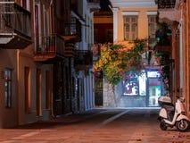 Weergeven van een streetin Nafplio, Griekenland, bij nacht die door bloemen en wijnstokken en geparkeerde autoped wordt verfraaid stock foto's