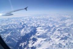 Weergeven van een vliegtuig over de alpen met sneeuw worden behandeld die stock fotografie